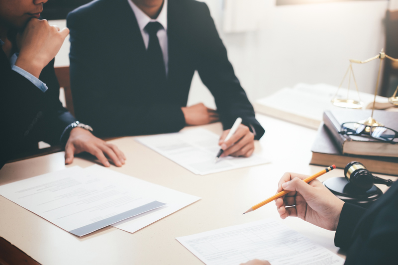Contract lawyers with a client at a table signing documents
