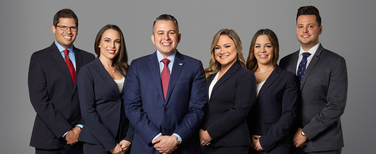 Five business attorneys in suits posing for a team photo