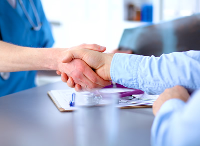 A healthcare lawyer and physician agreeing with a handshake while sitting at a desk