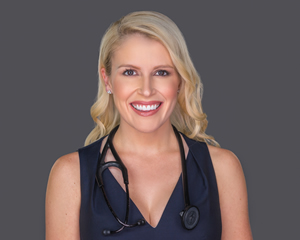 Solo headshot of a young blonde female doctor with a Stethoscope around her neck.