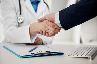Handshake between a healthcare lawyer and a doctor over a desk with a clipboard