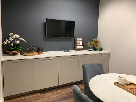 Break room area inside the law firm of Di Pietro Partners. There's a flat screen TV mounted on the wall above the counter and a round table with chairs.