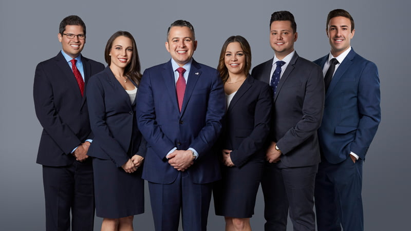 Professional group photo for the staff of Di Pietro Partners. The owner, David Di Pietro is in the middle in a navy blue suit and has several of his attorneys on standing on either side