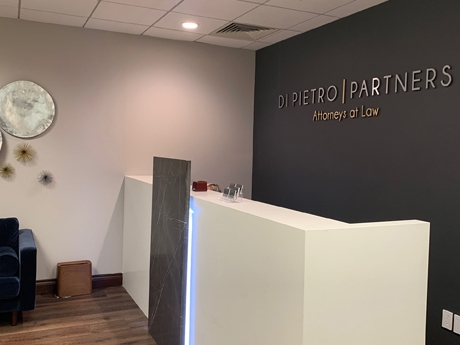 Law firm reception desk with a big sign behind it that says Di Pietro Partners attorneys at law