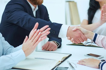 Visual link to the business litigation practice area page showing an attorney and client shaking hands over a contract