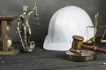 Visual link to the construction litigation practice area page showing a hard hat next to a judges gravel