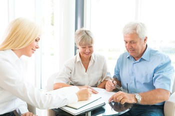 Visual link to the estate planning practice area page showing an elderly couple discussing a will with a female attorney