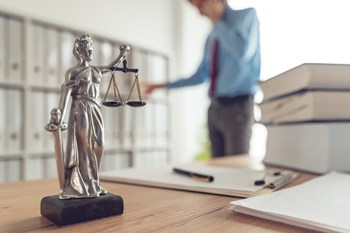 Visual link to the government investigations and white color crime practice area page showing a statute with the scales of justice