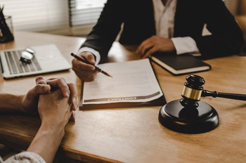 Visual link to the healthcare practice area page showing a client sitting at attorneys desk with a healthcare contract