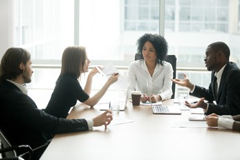 Visual link to the business law practice area page showing a group of attorneys discussing business at a table