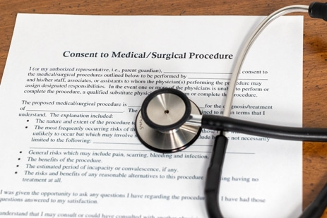 "Stethoscope on top of a document titled ""consent to medical/surgical procedure"" that symbolizes medical malpractice"