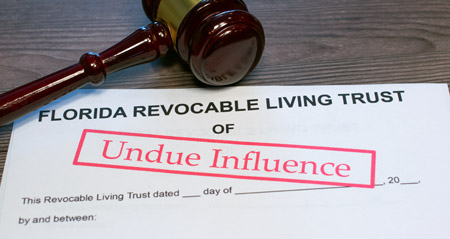 Paper document titled Florida Revocable Living Trust with the words undue influence stamped on it in red letters