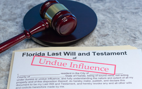 Paper document titled Florida Last Will and Testament with the words undue influence stamped on it in red letters