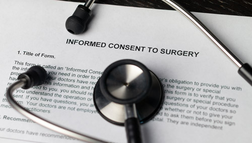 Stethoscope on top of a surgical consent form used to protect physicians from medical malpractice lawsuits