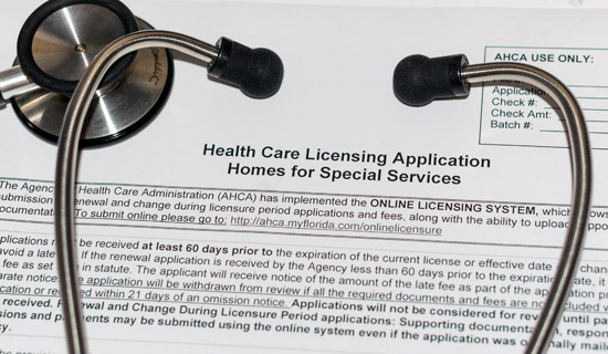 A physicians stethoscope on top of a form that's titled healthcare licensing application homes for special services