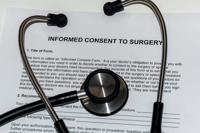 A physician's stethoscope on top of a blank form that's titled informed consent to surgery