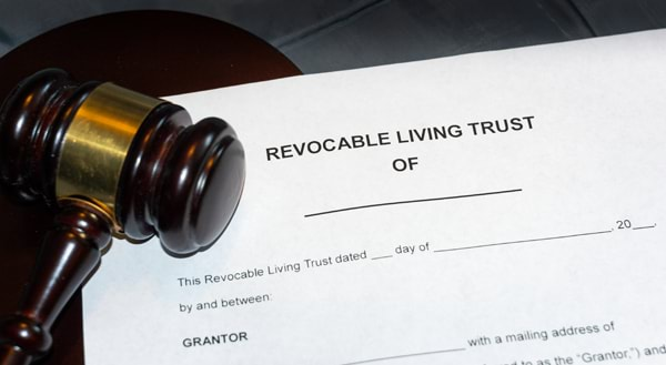 Gavel next to a blank example of a Revocable Living Trust symbolizing trust litigation
